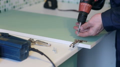man assembles furniture using a power screwdriver - stock footage