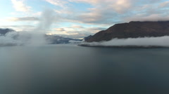 New Zealand High Fly Through Clouds Over Lake Towards Mountains at Sun Set 002 Stock Footage
