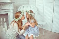 A happy mother and her daughter are going to kiss Stock Photos