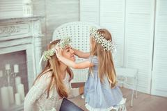 Daughter is putting a floral wreath on her mother - stock photo