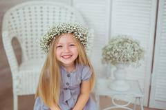 A happy girl with a floral wreath is grinning - stock photo