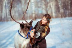 Portrait of a young girl with a reindeer in the winter - stock photo