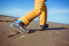 The legs of the boy running along the beach - stock photo