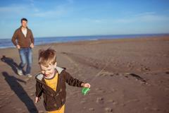 A boy and his dad are running on the sand - stock photo
