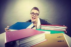 Happy crazy accountant with piles of binders. Stock Photos