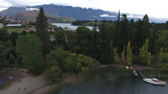 New Zealand Queenstown Fly Over Houses and Trees Towards Lake and Mountains - stock footage