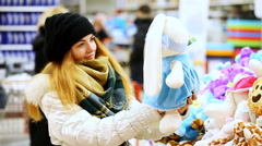 Beautiful young girl chooses a soft plush toy Stock Footage