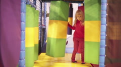 Small girl is spinning around herself in children's playroom. - stock footage