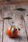 Tangerine with leaves on wooden background Stock Photos