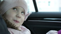 Little girl in winter pink hat and coat ape looking out the window in the car. - stock footage