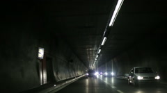 Cars traveling through the tunnel. Headlights in a darkness. - stock footage