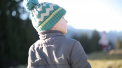 Little boy in a green winter hat and gray coat stands with his back to a camera. Stock Footage
