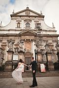 Bride and groom on the background of beautiful church. Beautiful old building Stock Photos