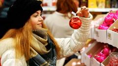 young girl chooses balls for Christmas tree - stock footage