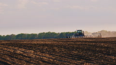 Tractor working in a field in the foreground of uncultivated land for sowing Stock Footage