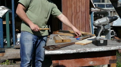 Carpenter nailing wood planks using hammer and steel nails - stock footage