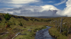 Looking along a mountain stream to Cotopaxi Volcano. Stock Footage