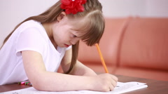 Downs Syndrome girl having speech therapy. Girl with Down syndrome painting - stock footage
