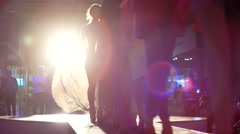 A group of girls on show of new clothes go on the catwalk in the light lamps. - stock footage