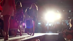 A group of young girls models walk the catwalk in the spotlight. - stock footage