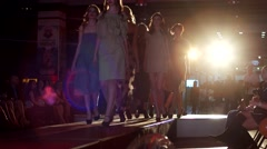 A group of young girls models walk the catwalk in the spotlight flash glowing Stock Footage