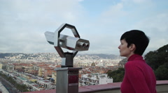 Woman tourist standing on the observation deck looking through a telescope Stock Footage