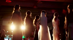 Girls turn on the catwalk posing for the audience at a night fashion show. - stock footage