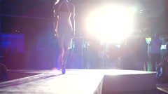 Girl in white dress in the ultra bright spotlight on the catwalk at fashion. - stock footage