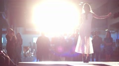 Light bright spotlights shining on a model in a white dress on the catwalk. Stock Footage