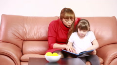 Mother and Downs Syndrome girl reading Stock Footage