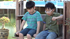 4k, Asian children sitting on swing chair outdoor Stock Footage