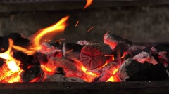 Firewood and hot coal in a grill, fire burning for the meat cooked - stock footage