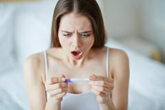 Shocked young woman looking at pregnancy test Stock Photos