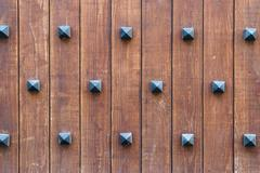 Old wooden wall with decorative rivets - stock photo