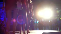 Slender sexy models in tight dresses illuminated by searchlights walking. Stock Footage