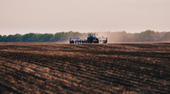 The tractor works in a field, sunflower sows. The camera pans for a tractor Stock Footage