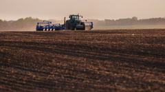 Tractor with drill goes through the field, carried out in spring seeding Stock Footage