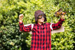 A kid is playing with a plane dressed with a costume of aviator Stock Photos