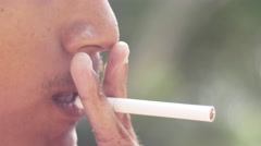 Close-up of a man lighting a cigarette and inhaling. - stock footage