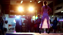 The girl in tight white dress on the catwalk with a flash of searchlights. - stock footage
