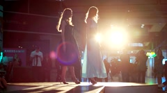 Two models in dresses come to the podium for defiles and presentations. - stock footage