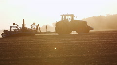 Tractor with drill goes through the field. Silhouette in backlit, beautiful rays - stock footage