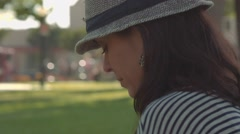 Woman sitting at a park texting on her cell phone Stock Footage