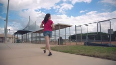 Woman walking by empty baseball field, steadicam shot - stock footage