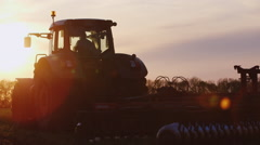 Tractor Silhouette, leave the setting sun - stock footage