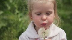 little girl blond blowing a dandelion - stock footage