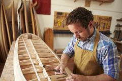 Man Building Bespoke Wooden Surfboard In Workshop Stock Photos