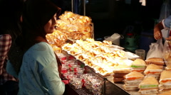 Muslim woman buys sweet bread from vendor Stock Footage