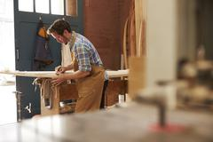 Carpenter Planing Bespoke Wooden Surfboard In Workshop - stock photo
