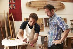 Carpenter With Apprentice Making Bespoke Wooden Surfboard - stock photo